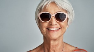 Studio shot of a senior woman wearing sunglasses against a grey background